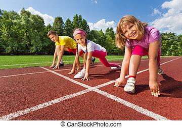Three smiling children in ready position on bending knee to run marathon in summer