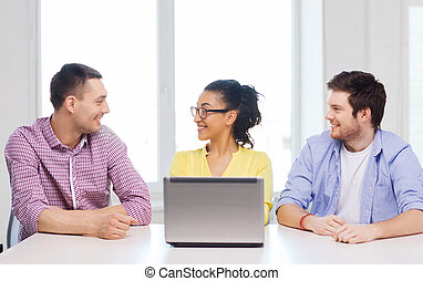 three smiling colleagues with laptop in office - education,...