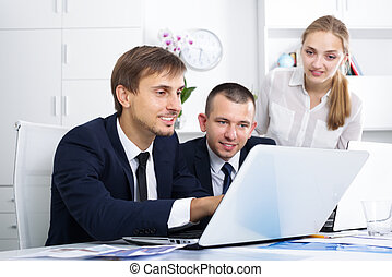 Three smiling coworkers working in company office