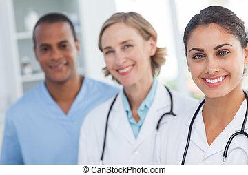 Three smiling doctors looking at the camera