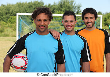 Three smiling footballers in front of goal