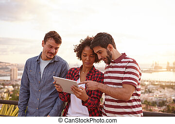 Three smiling friends looking at a tablet