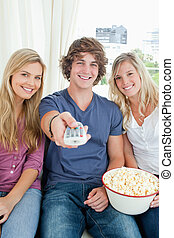 Three smiling friends with a bowl of popcorn and a tv remote looking at the camera