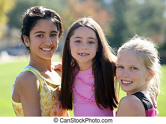 Three smiling girls of different race and age