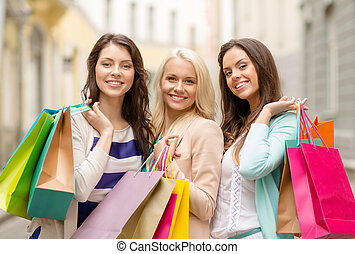 three smiling girls with shopping bags in ctiy - shopping, ...