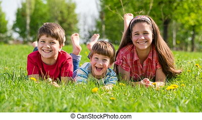Three smiling kids lying together on green grass