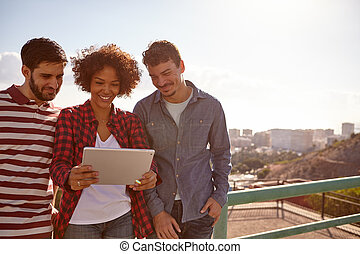 Three smiling millennials looking at a tablet