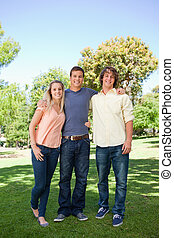 Three smiling students standing