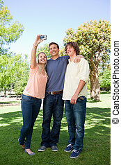 Three smiling students taking a pictures of themselves