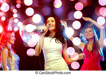 three smiling women dancing and singing karaoke - new year,...