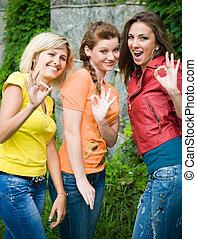 Three smiling women showing okey