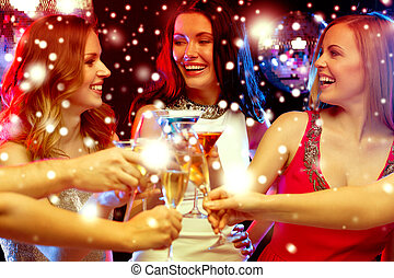 three smiling women with cocktails in club - new year,...