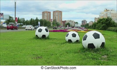 Three soccer balls by the road