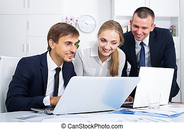 Three sociable coworkers working in company office
