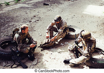 Three soldiers are sitting on tires and having rest. They had a good fight. Men want to keep their strenght for the next fight. One of them is holding firls while the other one is opening the bag.