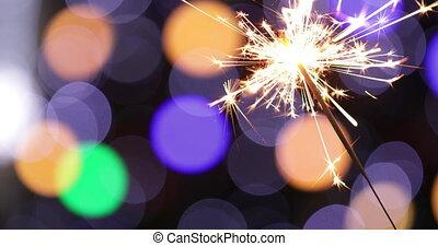 Three sparklers burning on a black background.