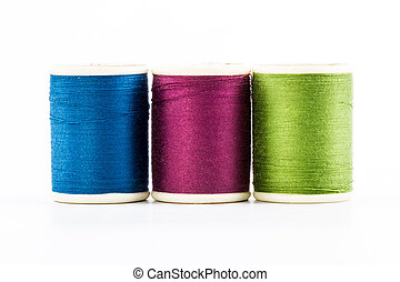 Three spools of sewing thread
