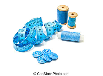 three spools of thread, buttons and meter closeup on white