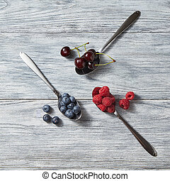 Three spoons with red juicy ripe berries - cherry, raspberry, blueberry and near them on a gray wooden background. Top view