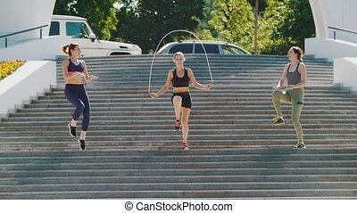 Three sports girls jump on the steps, one of them jumps on a...