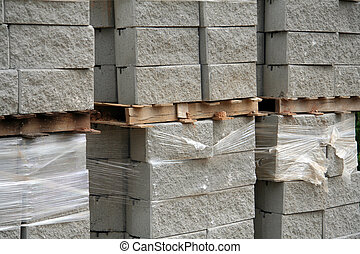 Three stacks of cement blocks on wooden palettes