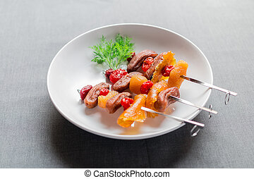 Three stainless steel skewer of dried mixed fruits on white...