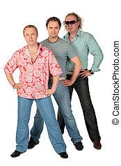 Three standing men. Music group.