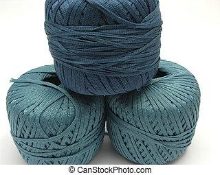Three stapled blue wool balls for needlework