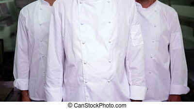 Three stern chefs looking at camera in a commercial kitchen