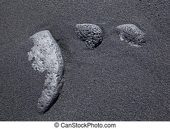 Three stones in the black sand