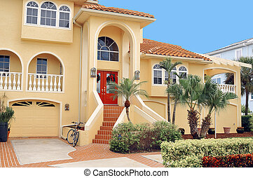 Large, elegant three story home in Tropical Florida seated on a waterfront canal. Dual stairs lead to the two door grand entryway.