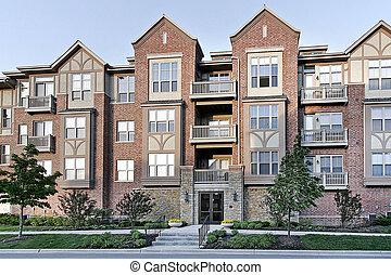 Three story tudor style condominium with stone entry