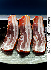 three strips of bacon in a pan