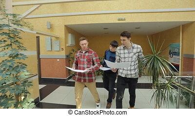 Three student walk with blueprint inside university of art.