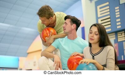 Three students boys with girl sit and talk in bowling club