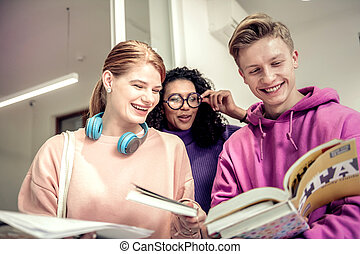 Three students feeling cheerful studying together near classroom