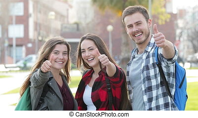 Three students gesturing thumbs up - Front view of three...