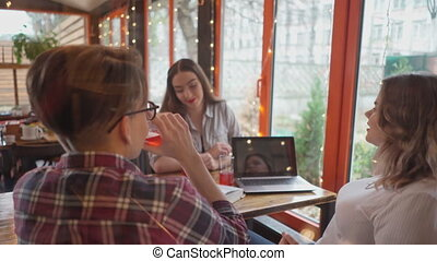 Three students guy and girls having discussion while study sitting in a cafe with lights running on the background as they sit at a table with different books on it. 4K footage.
