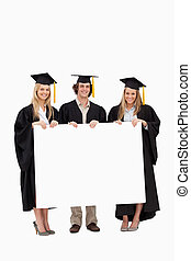 Three students in graduate robe holding a blank sign
