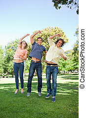 Three students jumping while raising an arm