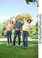 Three students jumping while raising an arm