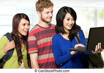 Three students looking at  a laptop