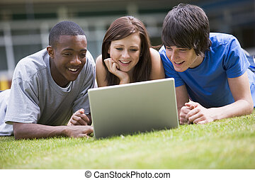Three students lying outdoors on lawn with laptop