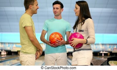 Three students play bowling, boy throws ball and misses tenpins