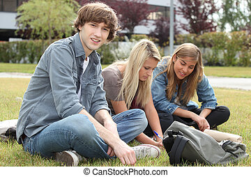 Three students sitting on the grass of a campus.