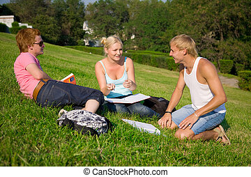 three students talking in the park