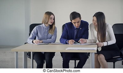 Three students talking sitting on table in classroom.
