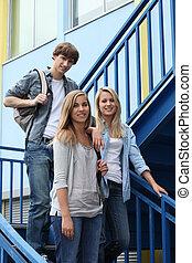 Three students walking down steps