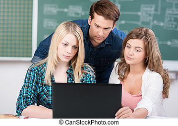 Three students working at a laptop