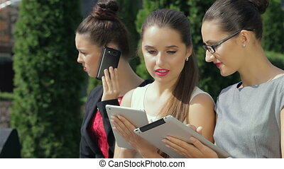Three successful business woman taking calls, working on the tablet, and discuss